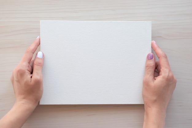 Quadro branco com as mãos para espaço de cópia. material de escritório escolar em fundo de madeira. de volta ao conceito de escola. vista superior pronta para seu projeto.