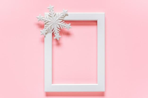 Quadro branco com floco de neve decoração em fundo rosa com espaço de cópia