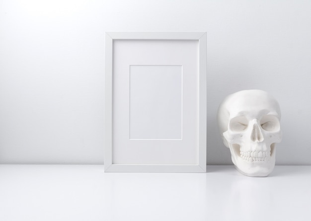 Quadro branco e crânio na estante de livros ou mesa