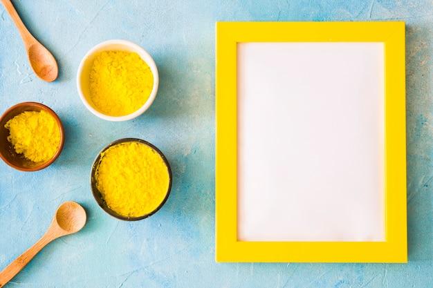 Quadro branco em branco com borda amarela perto do pó de cor holi em pano de fundo concreto