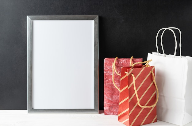 Quadro branco em branco com copyspace em uma mesa de madeira com sacos de papel