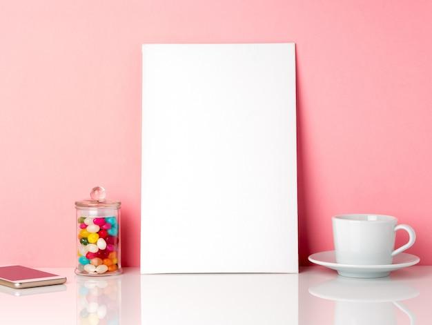 Quadro branco em branco e candys em jar, xícara de café ou chá em uma mesa branca contra a parede rosa