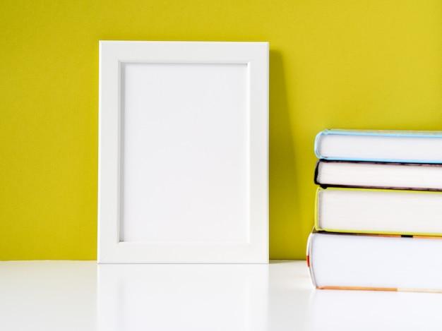 Quadro branco em branco e pilha de livros na mesa branca contra a parede de cor verde-oliva com espaço de cópia
