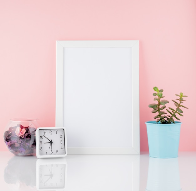 Quadro branco em branco e planta cacto, em uma mesa branca contra a cópia da parede-de-rosa