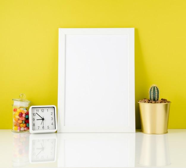 Quadro branco em branco, relógio, suculenta, doces na mesa branca agains