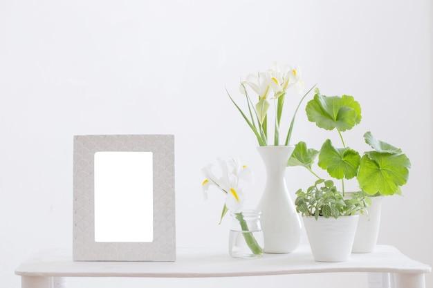 Quadro branco, plantas verdes e flores da primavera na prateleira na superfície branca