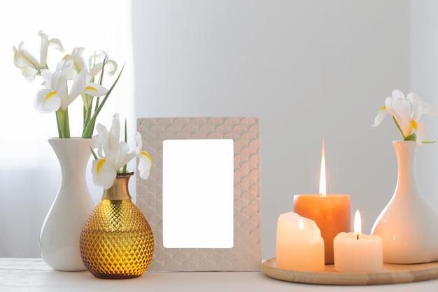 Quadro branco, queimando velas e flores na prateleira no fundo branco