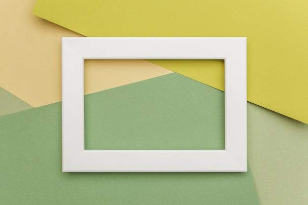 Quadro branco sobre fundo de papel geométrico tons verdes.