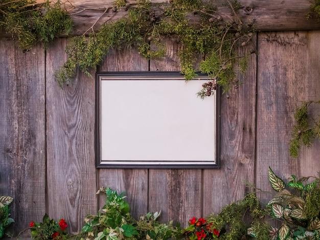 Quadro branco vazio em uma cerca de madeira cercado por plantas e flores