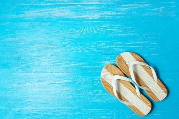 Quadro chinelos femininos elegantes sobre fundo azul de madeira, copyspace para texto, férias de verão.