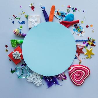 Quadro circular azul em branco sobre os itens de festa de aniversário no fundo