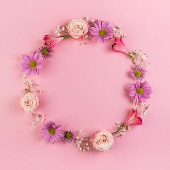 Quadro circular em branco feito com flores em fundo rosa