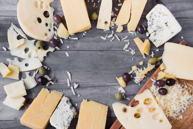 Quadro circular feito com diferentes tipos de queijo e azeitonas na mesa de madeira
