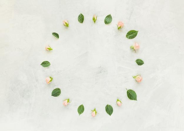 Quadro circular feito com folhas rosas e verdes na parede de concreto