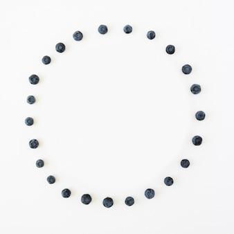 Quadro circular feito com mirtilos isolados no pano de fundo branco