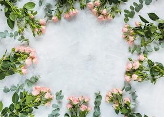 Quadro circular feito com monte de rosas em fundo de concreto