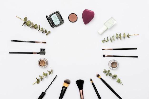 Quadro circular feito com pincéis de maquiagem e produtos cosméticos no fundo branco