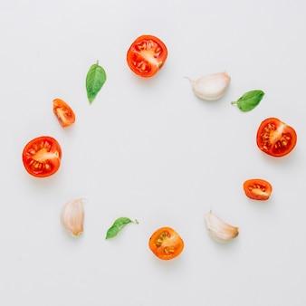 Quadro circular feito com tomates cereja; manjericão e alho cravinho em fundo branco
