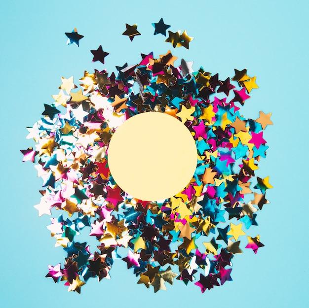 Quadro circular sobre o confete colorido da forma da estrela contra o fundo azul