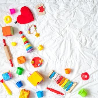 Quadro colorido brilhante dos brinquedos das crianças no fundo branco. vista do topo. lay plana. copie o espaço para te