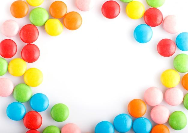 Quadro colorido das drageias coloridos dos doces de chocolate isoladas no branco.