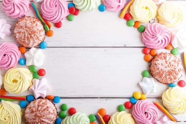 Quadro colorido de doces coloridos em branco de madeira.