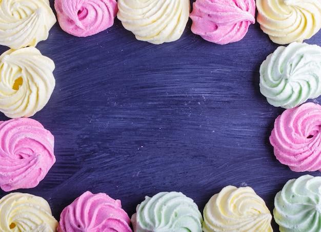 Quadro colorido de merengues coloridos no fundo de madeira preto.