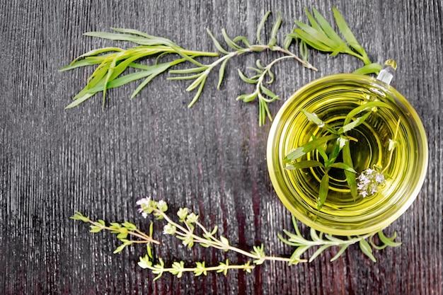 Quadro com chá de ervas em uma xícara de vidro, raminhos de estragão, alecrim e tomilho na placa de madeira