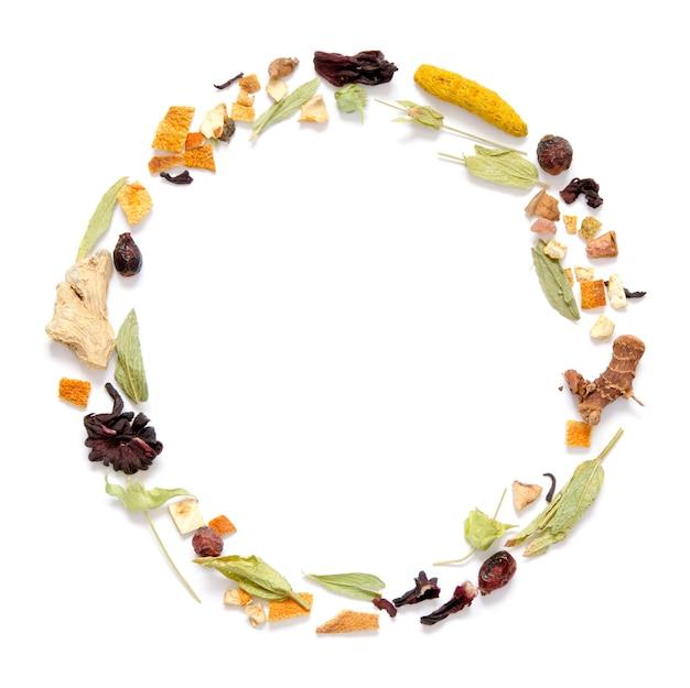 Quadro com chá de ervas, ervas secas e flores com pedaços de frutas e bagas.