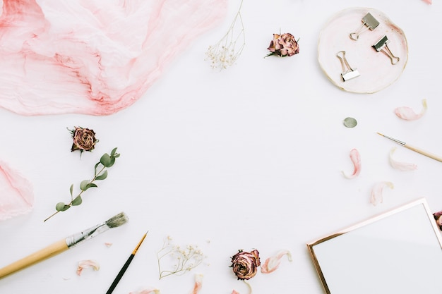 Quadro com espaço vazio, moldura, cobertor rosa, galhos de eucalipto e flores rosas em fundo branco. camada plana, vista superior