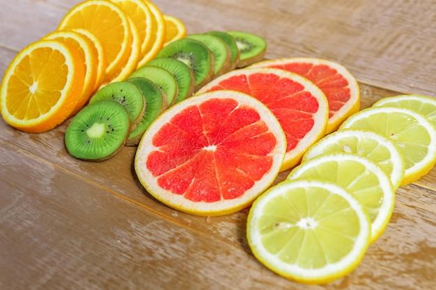 Quadro com fatia de laranjas, limões, kiwi, padrão de toranja em fundo de madeira.