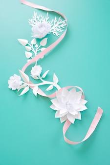 Quadro com flores de papel branco e fita rosa sobre fundo azul. corte de papel.
