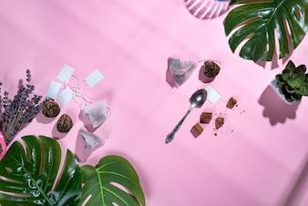 Quadro com folha tropical verde e xícara de chá, saquinho de chá e açúcar no fundo rosa pastel