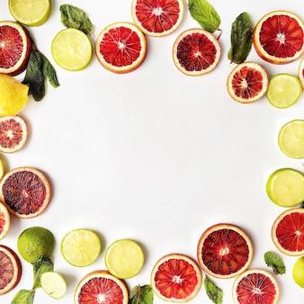 Quadro com laranjas vermelhas, limões amarelos, limas verdes e padrão de hortelã isolado no branco