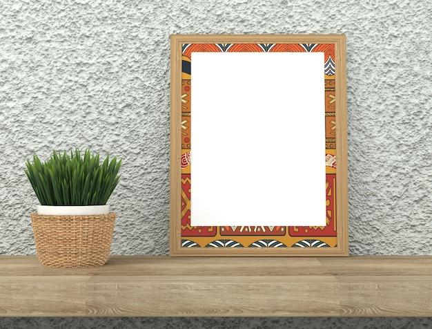 Quadro com ornamento étnico brilhante. grama verde em uma panela em uma mesa de madeira. parede emplastrada cinzenta áspera.