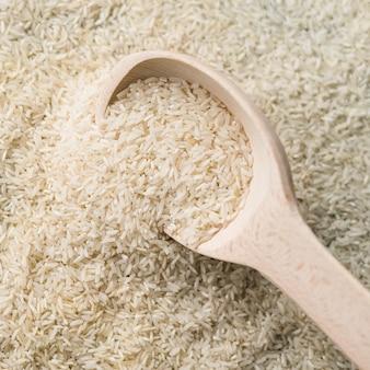 Quadro completo de arroz branco cru com colher de pau