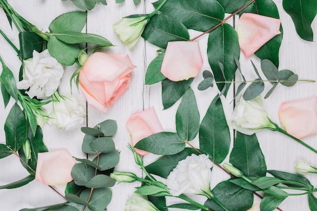 Quadro completo de folhas; eustoma e rosa rosas flores na mesa de madeira