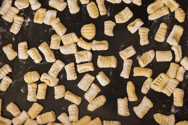 Quadro completo de nhoque de massas caseiras não cozidas na bancada da cozinha