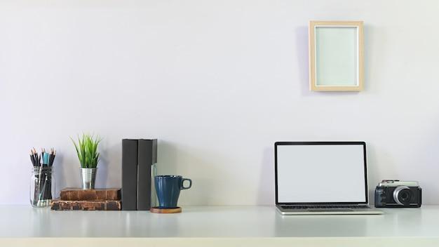 Quadro criativo laptop, câmera, café, caderno, lápis e foto moldura na mesa do espaço de trabalho.