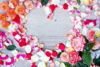 Quadro da forma do coração das flores de Rosa no fundo de madeira. Flat lay, vista de cima. Plano de fundo dia dos namorados.