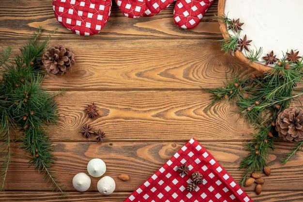 Quadro de acessórios de inverno festivo de ano novo e natal. bolo com creme branco, cones e ramos de coníferas, anis estrelado em um fundo de madeira.