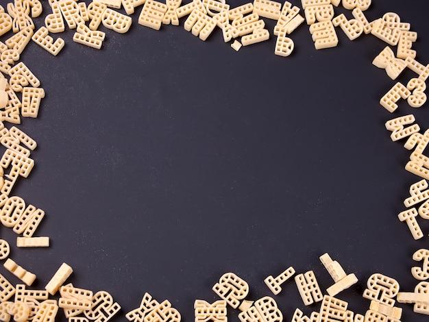 Quadro de alfabeto de macarrão cru em fundo preto