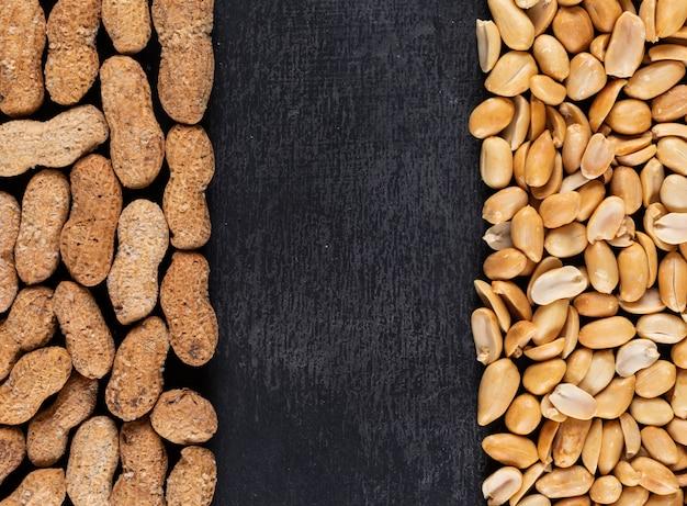 Quadro de amendoins crus e fritos de vista superior com espaço de cópia no centro no escuro