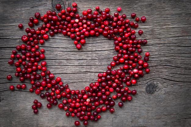 Quadro de arandos vermelhos maduros em uma opinião superior do close-up de madeira rústico do fundo do copyspace. cranberries em forma de coração.