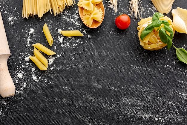 Quadro de arranjo de massas alimentícias não cozidas em fundo preto, com espaço de cópia