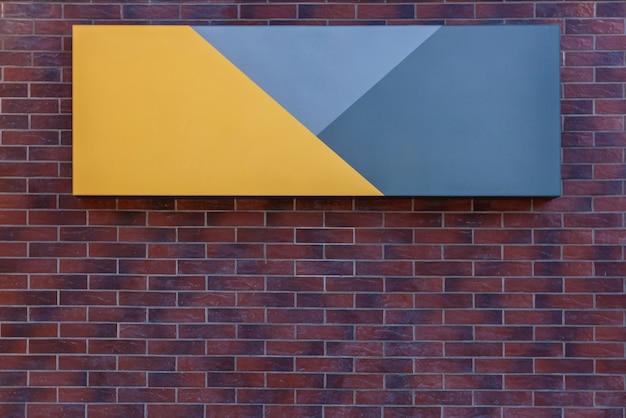 Quadro de avisos amarelo cinza, preso à parede de tijolos externa do prédio.