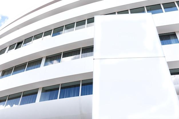 Quadro de avisos branco vazio no exterior do prédio branco de escritórios modernos.