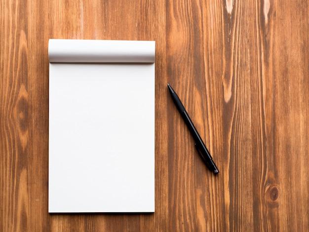 Quadro de avisos com a folha vazia para notas e lápis no fundo de madeira em branco abstrato