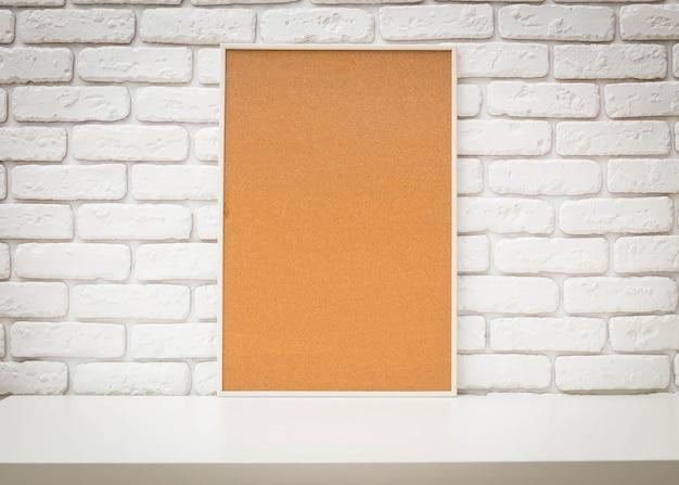 Quadro de avisos de cortiça na parede de tijolo branco