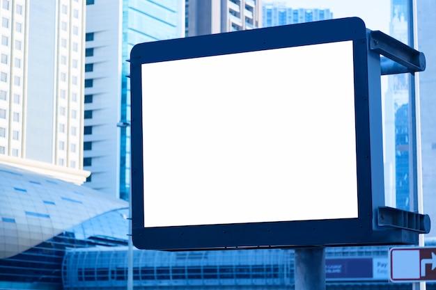 Quadro de avisos vazio em branco na rua da cidade em dubai, uae contra arranha-céus. em tons de azul